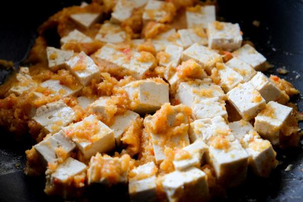 Verhit een scheutje olie in een wok op hoog vuur. Bak hierin het sjalot-knoflook-peper-gember-mengsel, gedurende 1-2 minuten. Voeg de gesneden tofu toe en bak.  De tofu moet een beetje bruin aan de buitenkant worden.