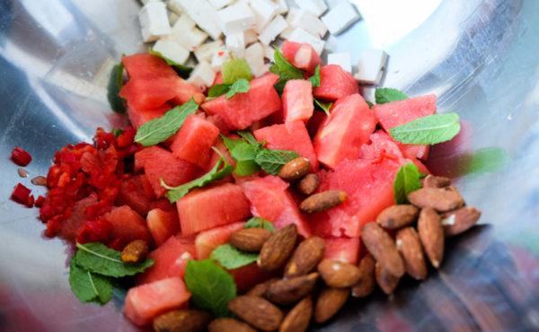 Haal de muntblaadjes van de takjes, was ze en voeg ze samen met de meloen, komkommer, amandelen en geitenkaas in een grote (salade)bak.