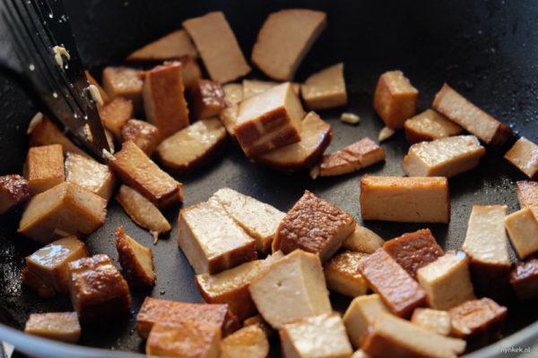 Snijd de gerookte tofu in blokjes en bak deze met wat olie tot alle kanten bruin zijn. Gooi deze bij de salade.