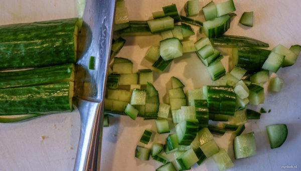 Snijd de sla en paprika in stukjes en de komkommer en courgette in kleine blokjes. Doe de gesneden groenten in een grote (salade)bak waar je alles nog makkelijk in kunt mengen.