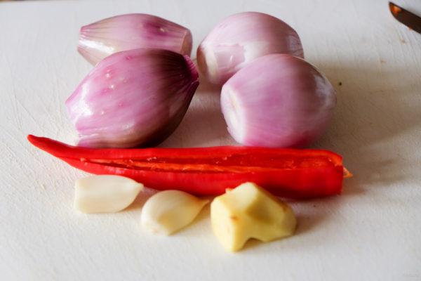 Schil de sjalotjes, gember en knoflook. Haal de zaden uit de rode peper.