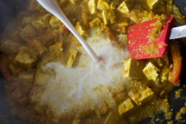 Voeg de kokosmelk toe en breng weer aan de kook. Leg je een hand spinazie in de wok en laat deze een slinken in de saus. Voeg dan pas de volgende hand spinazieblaadjes toe, totdat alles erin zit. Roer de saus goed door, breng desnoods nog op smaak met zout en peper.