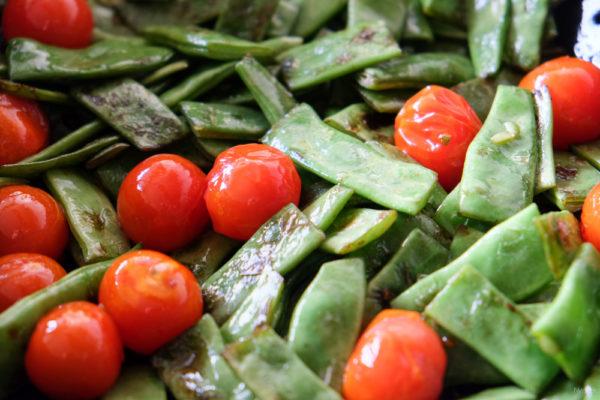 Voeg de cherrytomaten toe aan de snijbonen en bak deze mee totdat de velletjes een beetje knappen.